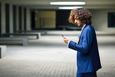 Young fashionable businessman with curly hair looking at smartphone - p300m2070005 von Javier Sánchez Mingorance