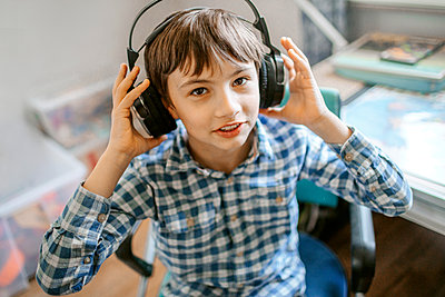 Boy listening music through headphones at home - p300m2267834 by Oxana Guryanova