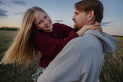 Father and daughter enjoying in field during sunset - p300m2281732 by Ekaterina Yakunina