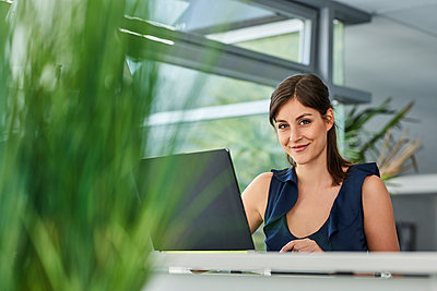 Young woman in office working on laptop  - p890m1440363 by Mielek