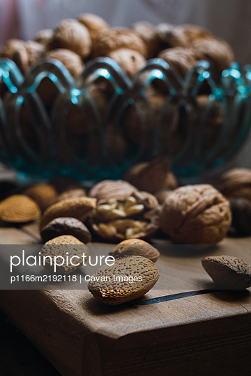 walnuts and almonds in a blue glass bowl on a rustic wooden table - p1166m2192118 by Cavan Images