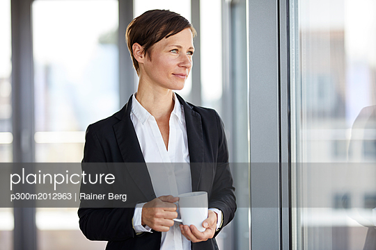 Businesswoman in office with cup of coffee  looking out of window - p300m2012963 von Rainer Berg