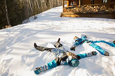 Siblings making snow angels - p1192m1023845f by Hero Images