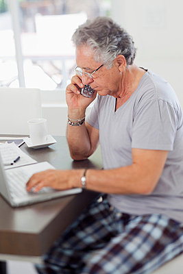 A senior man using a laptop and talking on a cordless phone at home - p30120290f by Jonathan Gelber