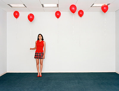 Young woman holding balloon in office - p3721920 by James Godman
