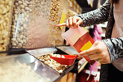 Midsection of woman filling pistachio nuts in paperbag at supermarket - p426m1017988f by Maskot