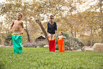 Mother and two sons having a sack race, County Park, Los Angeles, California, USA - p924m973946f by David Jakle