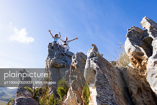 Two children climbing on top of large sandstone rock formations on a nature trail. - p1100m2300933 by Mint Images