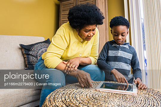 Boy and grandmother using digital tablet while sitting in living room at home - p1166m2279400 by Cavan Images