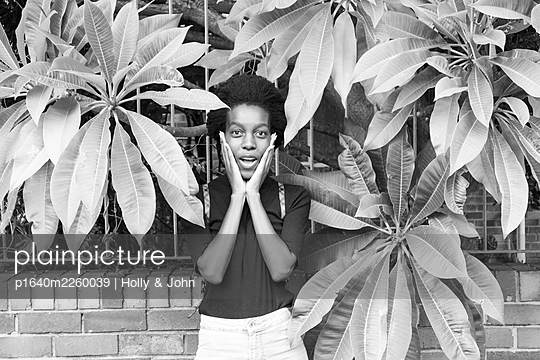 African woman between leaves, portrait - p1640m2260039 by Holly & John