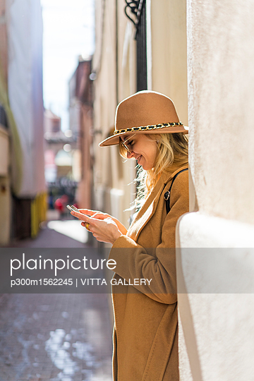 Fashionable young woman in a lane using cell phone - p300m1562245 by VITTA GALLERY