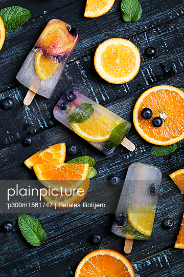 Homemade detox popsicles with blueberries, orange slices and mint leaves on black wood - p300m1581747 von Retales Botijero