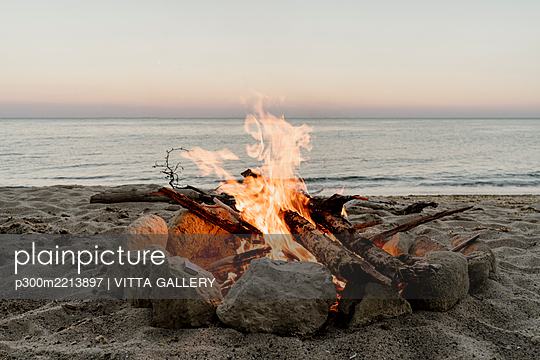 Campfire on empty beach during sunset - p300m2213897 by VITTA GALLERY