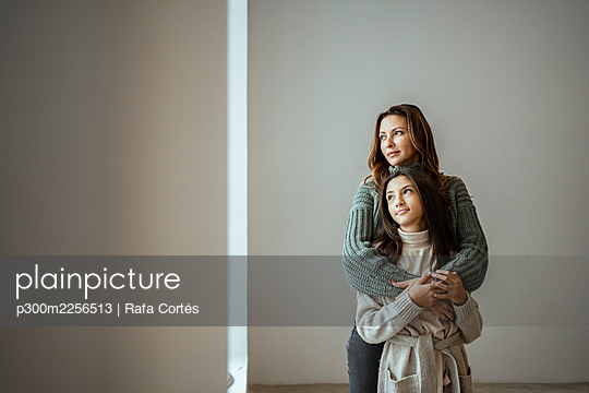 Mother and daughter looking away while embracing each other against wall at home - p300m2256513 by Rafa Cortés