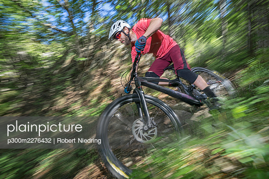 Male athlete moving down while riding bicycle in forest - p300m2276432 by Robert Niedring