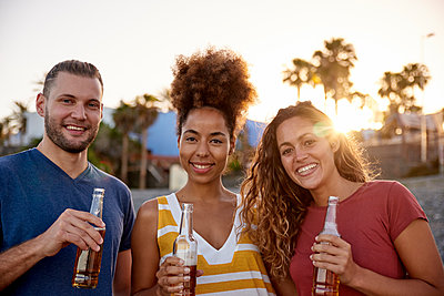Group picture of three friends with beer bottles on the beach at sunset - p300m1469926 by Pablo Calvo