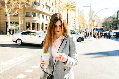 Spain, Barcelona, young woman with coffee to go standing at roadside looking at cell phone - p300m1587914 by Valentina Barreto