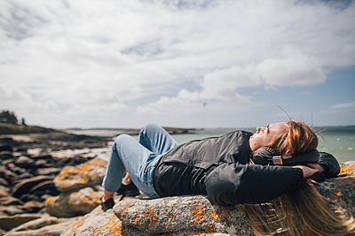 France, Brittany, Landeda, young woman wearing headphones lying at the coast - p300m2005589 by Gustafsson