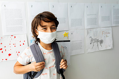 Boy wearing mask standing against papers stuck on wall in school - p300m2203146 by Valentina Barreto