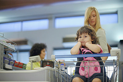 Young girl in grocery store with woman at check-out - p641m717226f by Floresco Productions