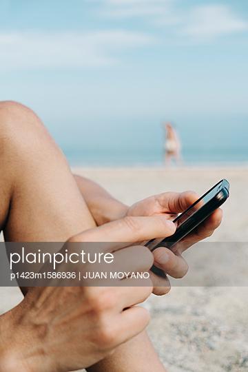 Mann benutzt sein Smartphone am Strand - p1423m1586936 von JUAN MOYANO