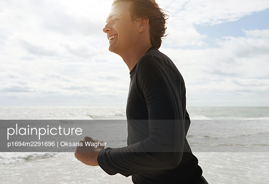 Happy young man running on the beach close to the ocean in the morning  - p1694m2291696 by Oksana Wagner