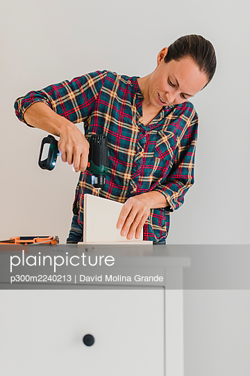 Mid adult woman using electric drill while working by cabinet at home - p300m2240213 by David Molina Grande
