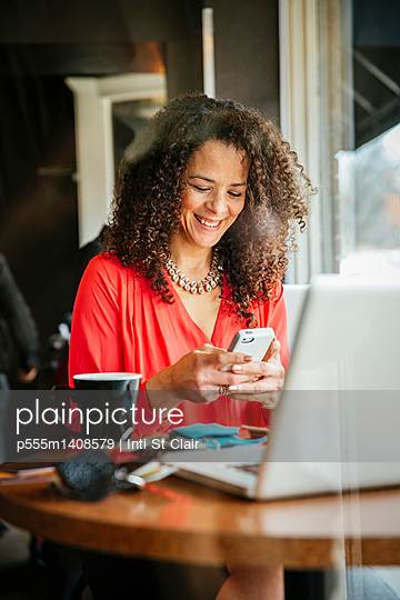 Businesswoman using cell phone in cafe - p555m1408579 by Inti St Clair photography