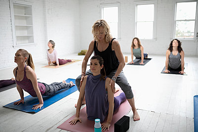 Yoga instructor helping woman practicing upward facing dog pose in yoga class - p1192m1583339 by Hero Images