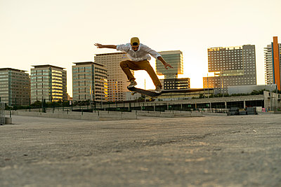 Young man doing a skateboard trick in the city at sunset - p300m2028710 by VITTA GALLERY