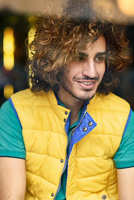 Portrait of smiling young man with beard and curly hair wearing yellow waistcoat looking out of window - p300m2070479 von Javier Sánchez Mingorance