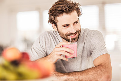 Young man smiling and drinking a fruit smoothie - p300m2167495 by Floco Images