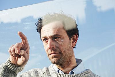 Portrait of man pointing on glass pane - p300m2213745 by Jo Kirchherr