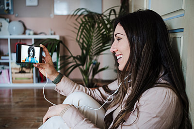 Beautiful woman having video call with friend on smart phone while sitting at home - p300m2274006 by Eva Blanco