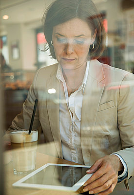 Portrait of business woman using tablet computer at coffee break - p300m926673f by Uwe Umstätter