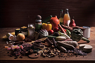A variety of fresh and processed foods in a heap on a table - p301m714329f by Larry Washburn
