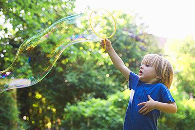 Boy making oversized bubble in backyard - p42916178f by Ghislain & Marie David de Lossy