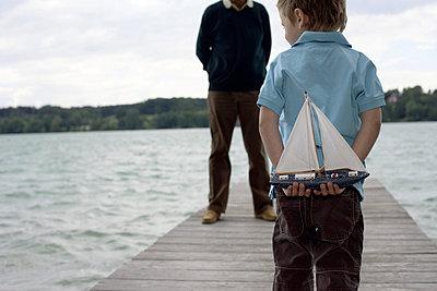 Kleiner Junge steht mit einem Spielzeugboot hinterm Rücken vor einem Mann auf einem Holzsteg - Freizeit - See - Familie - p4732509f von Stock4B
