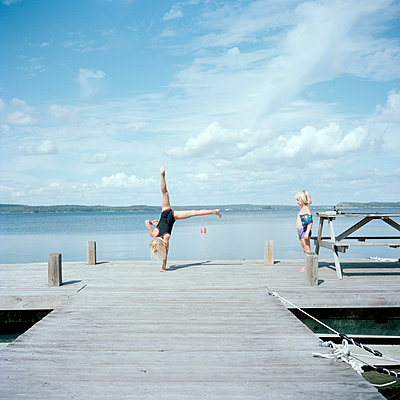Boy and girl playing on jetty - p528m1075337f by Johan Willner