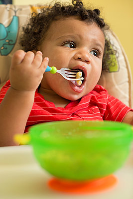 Mixed race toddler boy eating in high chair - p555m1459379 by Roberto Westbrook