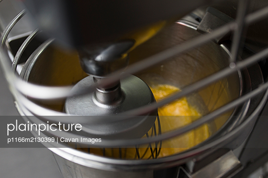 Mixer whipping egg yolks in bowl - p1166m2130399 by Cavan Images