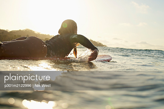 Female surfer paddling out on sunny, sunset ocean - p301m2122996 by Nik West