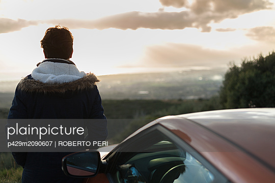 Man resting against car on roadside, enjoying view on hilltop - p429m2090607 by ROBERTO PERI