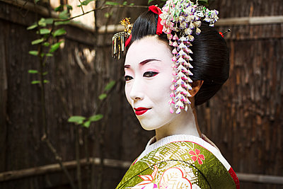 A woman dressed in the traditional geisha style, wearing a kimono and obi, with an elaborate hairstyle and floral hair clips, with white face makeup with bright red lips and dark eyes.  - p1100m1185718 by Mint Images