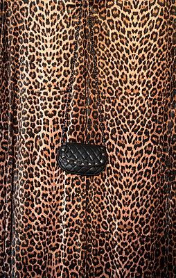 Handbag in front of animal print fabric - p1199m2181428 by Claudia Jestremski