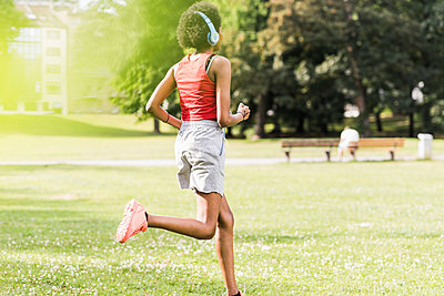 Young woman with headphones running in park - p300m2024142 by Uwe Umstätter