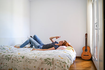 Young woman at home chilling in bedroom and using her smartphone - p300m2118474 by VITTA GALLERY