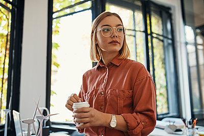 Businesswoman having a coffee break in office - p300m2144864 von Zeljko Dangubic