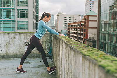 Woman stretching before exercise in the city, Vancouver, Canada - p300m2169966 by Crystal Sing
