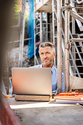 Smiling architect using laptop while sitting at construction site - p300m2256444 by Peter Scholl